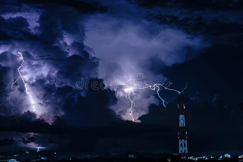 在手机天线塔的分叉的闪电在晚上 库存照片