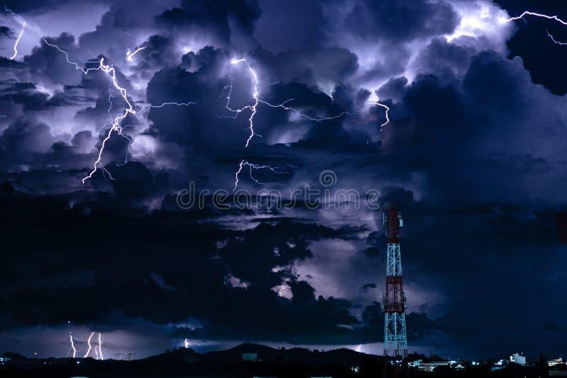 在手机天线塔的分叉的闪电在晚上 免版税库存图片