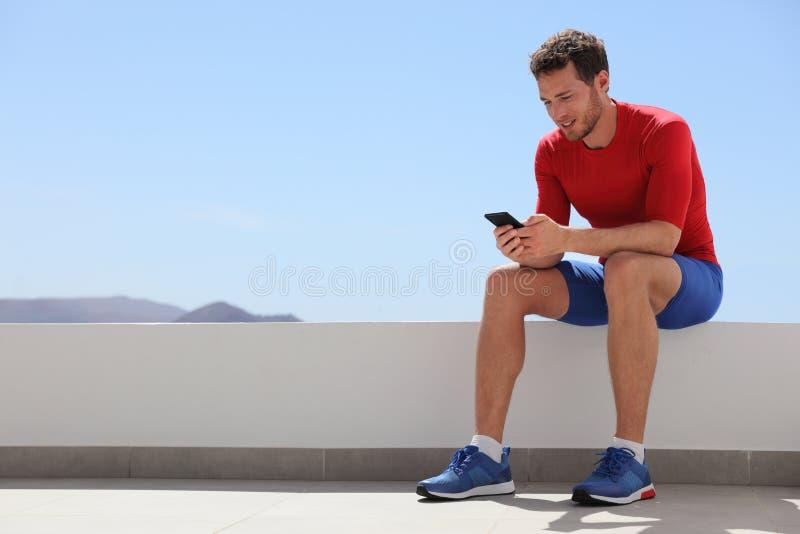 在手机屏幕在家或室外健身房的运动员人观看的录影 技术和体育运动员藏品手机 愉快的适合 免版税库存图片