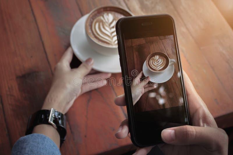 在手机显示屏上使用拿铁咖啡智能手机拍照的女孩 免版税图库摄影