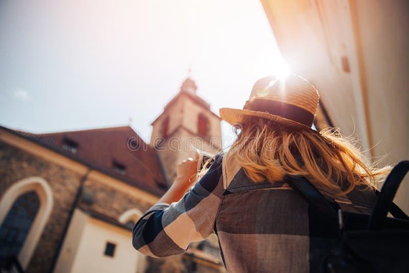 在手机智能手机的年轻女人旅游照相在日落的欧洲 图库摄影