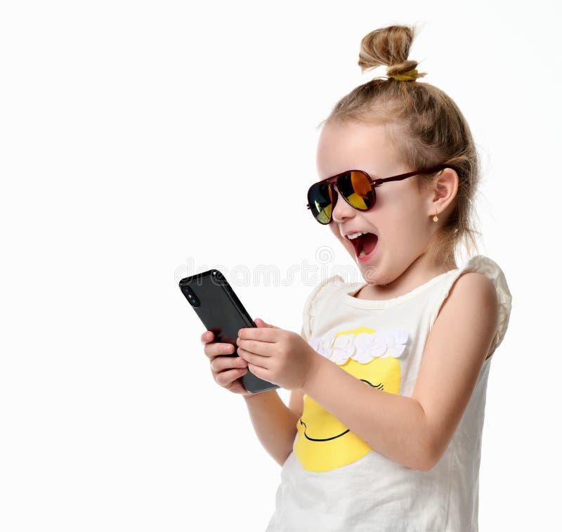在手机机动性的女孩读书短信的sms与在太阳镜的触摸屏 免版税库存照片