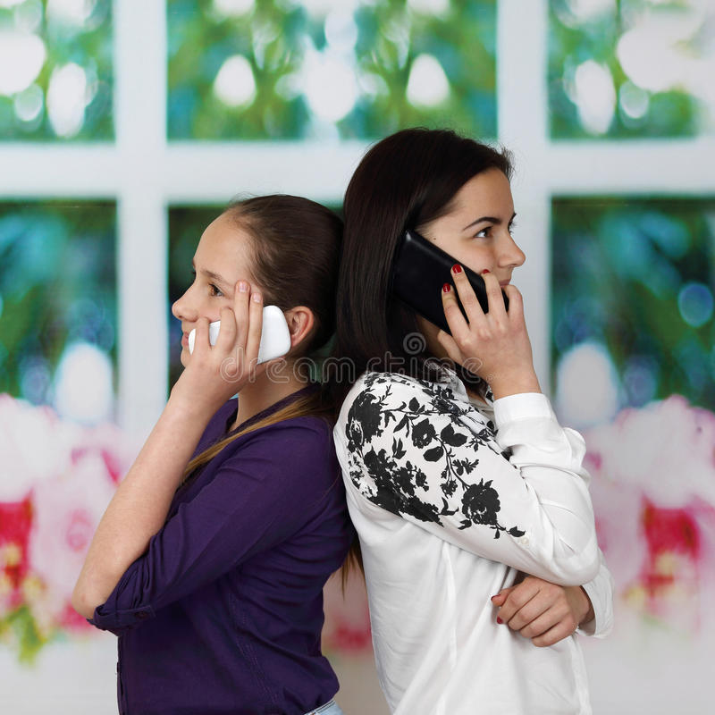 在手机的两个姐妹tolk 免版税库存照片