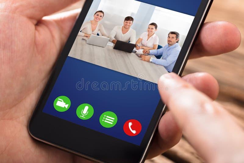 在手机的人视讯会议 图库摄影