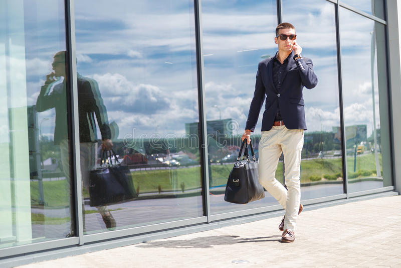 在手机的典雅的商人电话,当走带着手提箱机场外时 图库摄影