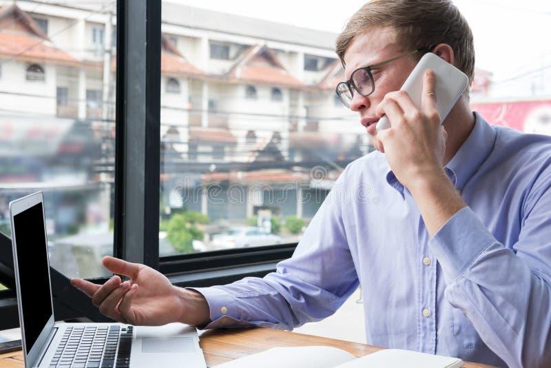 在手机的商人谈话在办公室 在sm的年轻人电话 库存图片