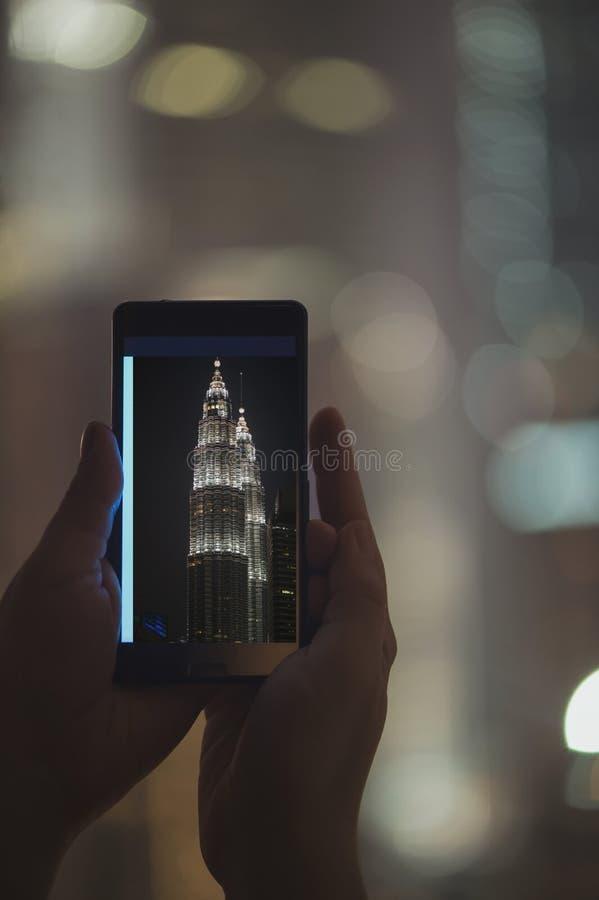 在手机的女性被采取的图片夜塔天然碱 在马来西亚和吉隆坡附近的旅行 免版税库存图片