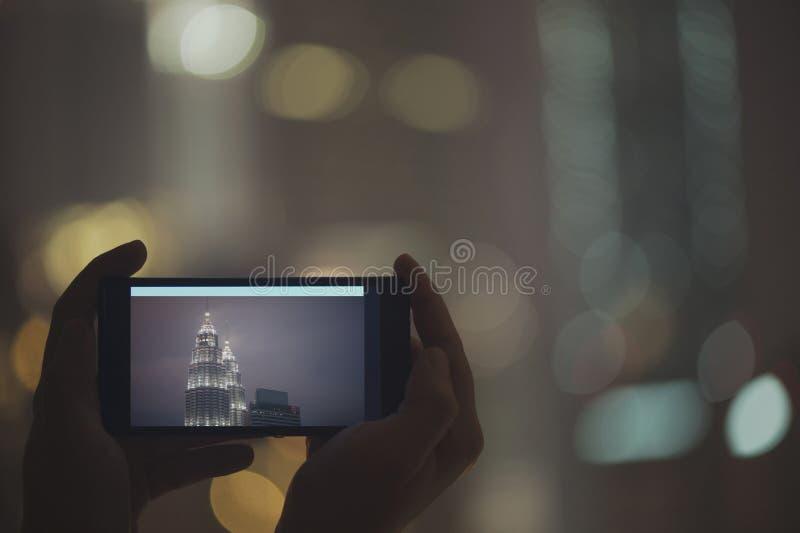 在手机的女性被采取的图片夜塔天然碱 在马来西亚和吉隆坡附近的旅行 库存图片