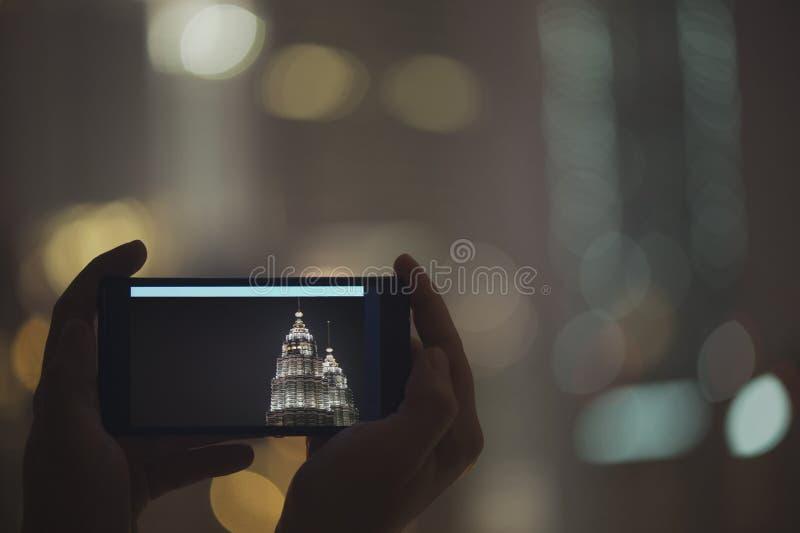 在手机的女性被采取的图片夜塔天然碱 在马来西亚和吉隆坡附近的旅行 库存照片