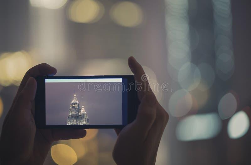 在手机的女性被采取的图片夜塔天然碱 在马来西亚和吉隆坡附近的旅行 免版税库存照片