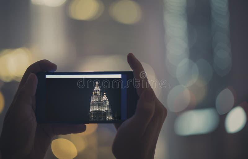 在手机的女性被采取的图片夜塔天然碱 在马来西亚和吉隆坡附近的旅行 免版税图库摄影