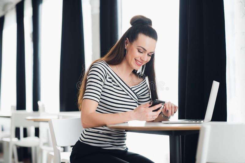 在手机的微笑的有吸引力的妇女读书正文消息在餐馆 库存图片