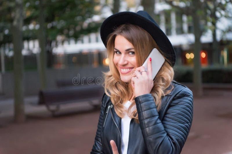 在手机的愉快的妇女谈话在巴黎,法国 有长的金发的,发型,秀丽肉欲的妇女 现代生活,新的technol 库存照片