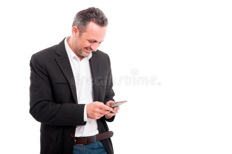 在手机的愉快的年轻商人读书正文消息 免版税库存图片