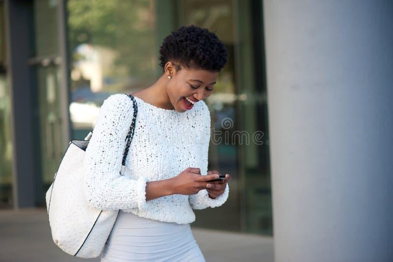 在手机的愉快的年轻非洲妇女读书文本 库存照片