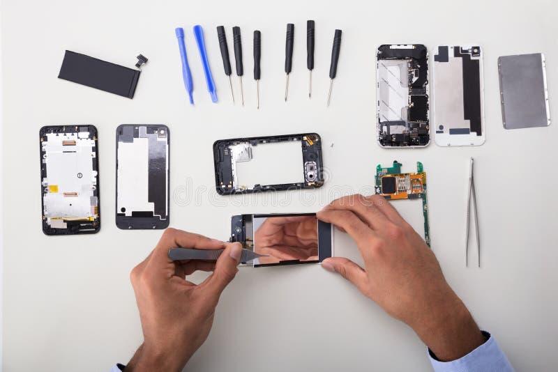 在手机的技术员定象损坏的屏幕 库存照片