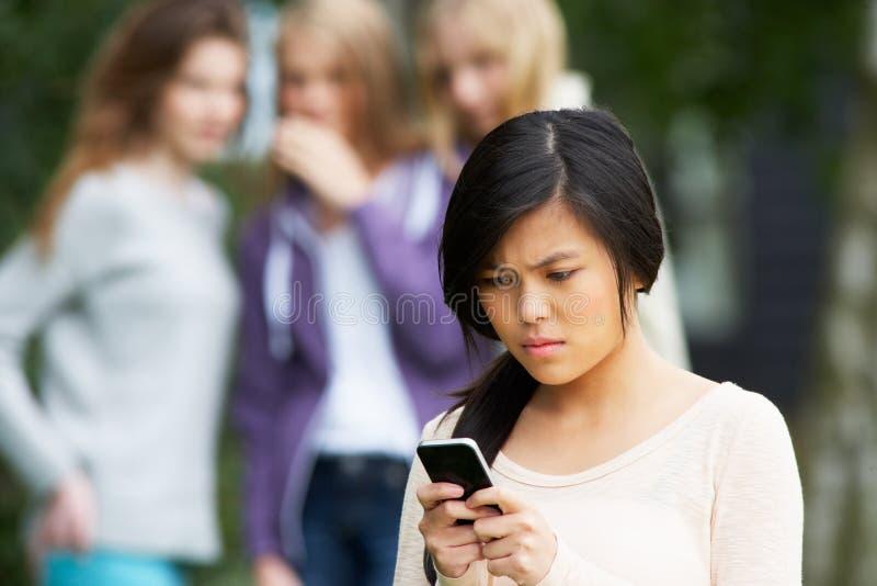 在手机的正文消息被胁迫的十几岁的女孩 免版税库存图片