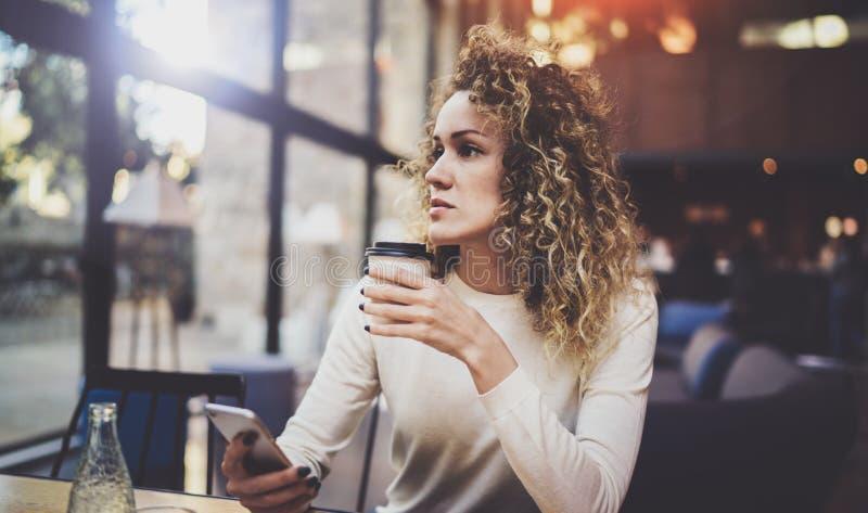 在手机的迷人的美好的少妇读书电子邮件在咖啡店的休息时间 Bokeh和火光 图库摄影