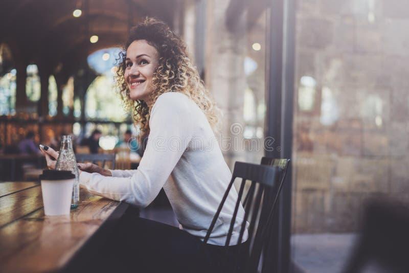 在手机的迷人的美好的少妇读书电子邮件在咖啡店的休息时间 Bokeh和火光 免版税库存图片