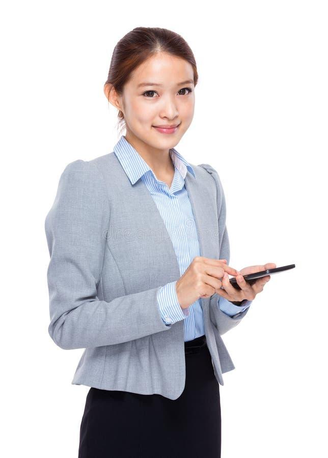 在手机的年轻女实业家接触 库存图片