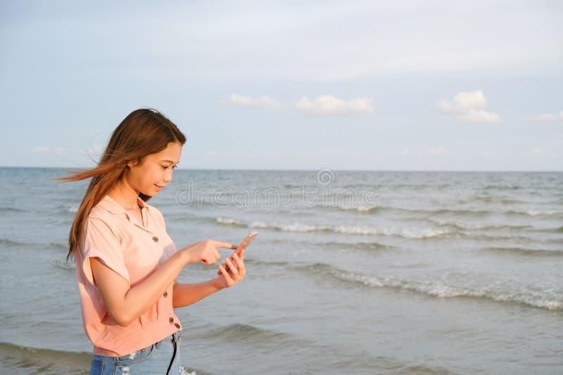 在手机身分在海滩,夏天旅行概念的年轻女人接触 库存图片