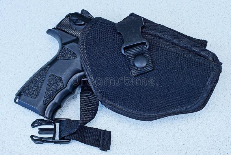 在手枪皮套的大黑枪在一张灰色桌上说谎 免版税库存图片