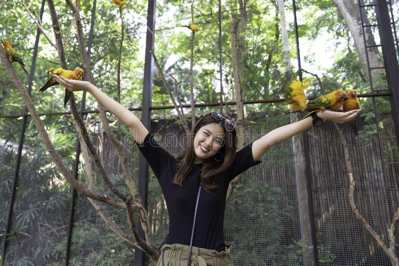 在手边享用与爱鸟和身体的亚裔美女 图库摄影