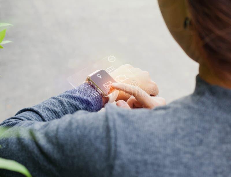 在手边使用巧妙的手表的特写镜头妇女显示infographic hol 免版税库存图片