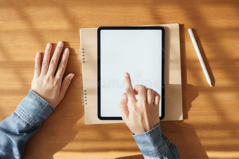 在手边使用有白色屏幕触摸屏幕技术项目的亚裔妇女片剂 它投入了书桌和笔记本 免版税库存图片
