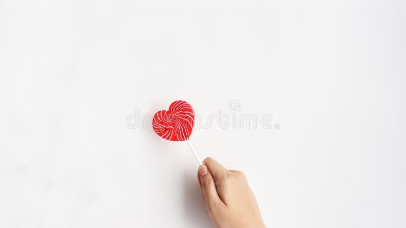 在手边关闭心脏棒棒糖 库存照片
