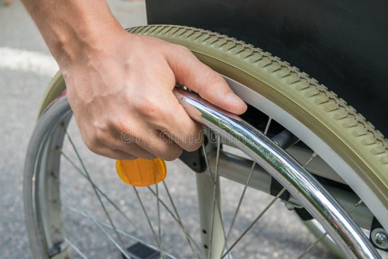 在手边关闭看法轮椅的有残障的人 库存图片
