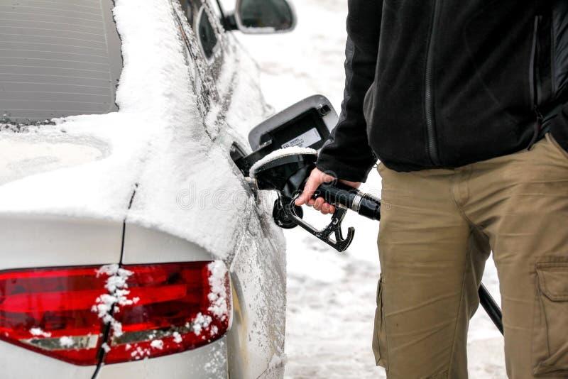 在手边填装他积雪的柴油汽车汽油箱的人在燃油泵、细节和汽油喷管 库存照片