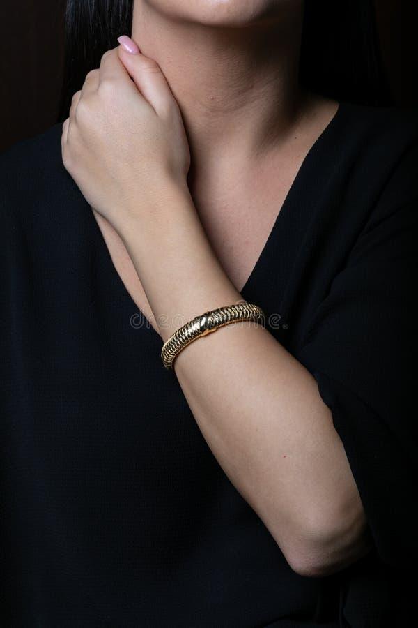 在手边女性,柳条,金银铜合金镯子,在黑背景 库存照片