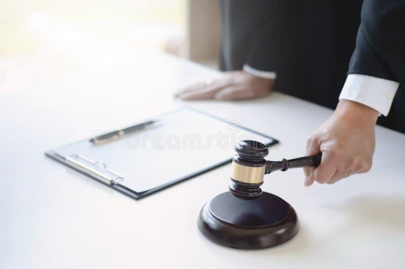 在手边工作在有正义锤子的法庭的成熟律师 免版税库存图片