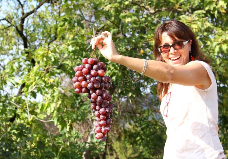 在手边微笑用葡萄的妇女 库存照片