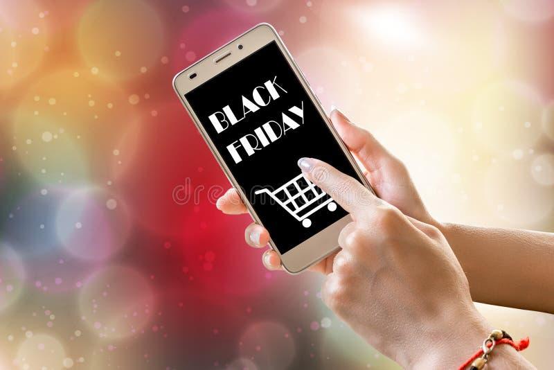 在手边拿着智能手机的黑星期五销售文本 免版税库存图片