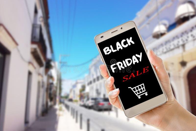 在手边拿着智能手机的黑星期五销售文本 库存照片
