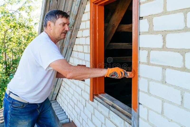 在手边拿着油漆刷的特写镜头视图 使用油漆刷的老人绘画木窗口 修理老房子外部  免版税库存图片