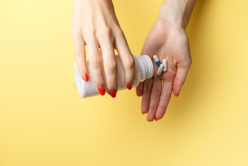 在手边拿着药片的妇女 o 溢出一个瓶的痛苦的手药片在黄色背景的 库存图片