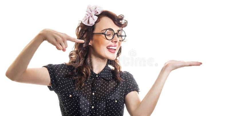 在手边指向与她的手指某事的少妇 免版税图库摄影