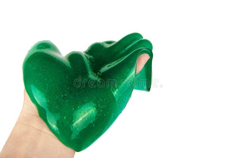 在手边流动液体绿色的软泥 背景查出的白色 库存图片