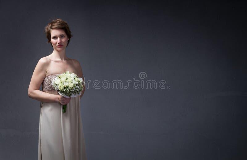 在手边等待与花的新娘妇女 免版税库存照片