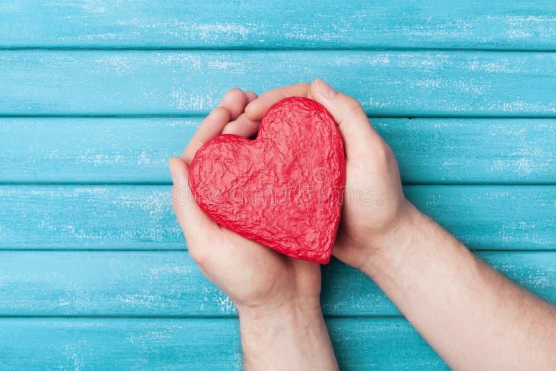 在手顶视图的红色心脏形状 健康,捐赠器官、捐款人、希望和心脏病学概念 可用的看板卡日文件华伦泰向量 免版税库存图片