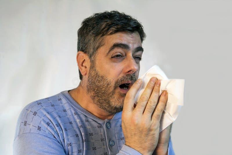 在打喷嚏与强的寒冷的睡衣的人中型年龄 免版税库存照片