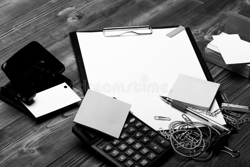 在打孔器,贴纸,弹性附近截去与白皮书的文件夹 免版税库存图片