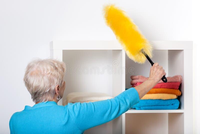 在打扫灰尘家具期间的年长夫人 图库摄影
