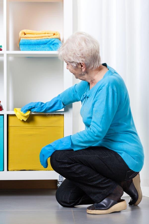 在打扫灰尘家具期间的年长妇女 免版税库存照片