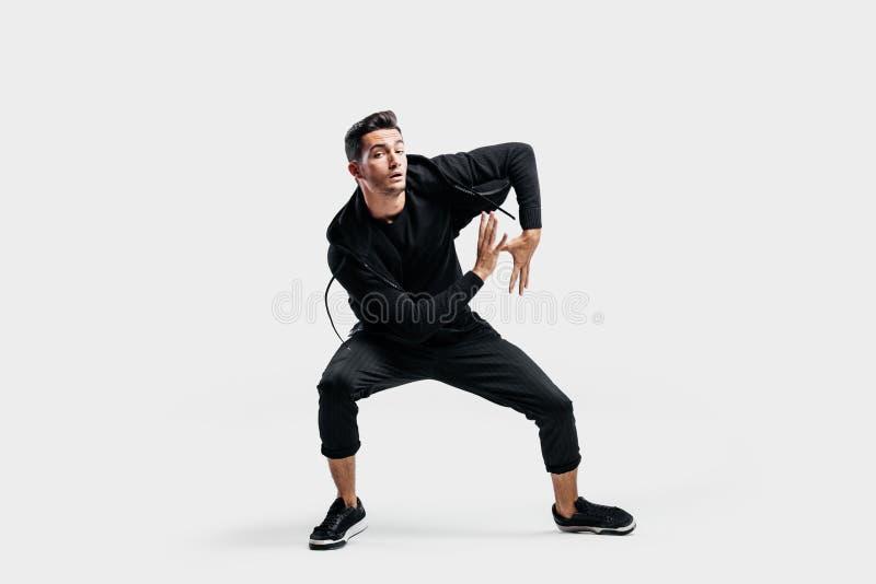 在打扮的深色头发的年轻人黑色衣服跳舞街道舞蹈 他做风格化运动用他的手 免版税库存照片