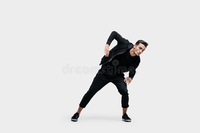 在打扮的英俊的年轻人黑色衣服跳舞街道舞蹈 他做风格化运动用他的手 库存图片