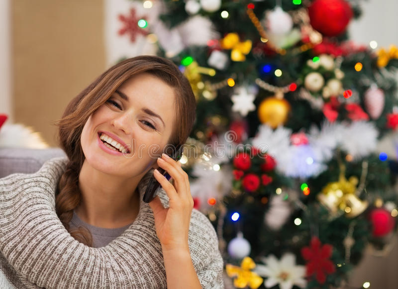 在打电话的圣诞树附近的愉快的妇女 免版税图库摄影